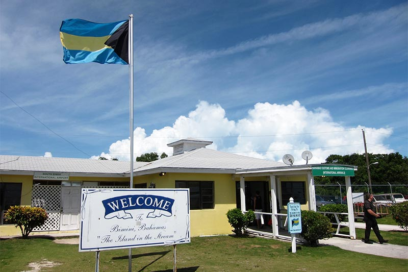 Building with Bahamian flag in front and person walking away.